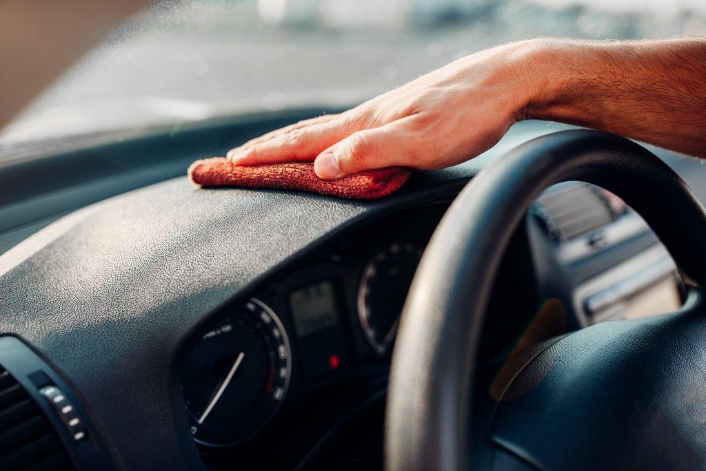 Male hands cleans auto, car dashboard polishing